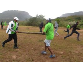 People running carrying poles