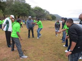People doing team building exercise in field